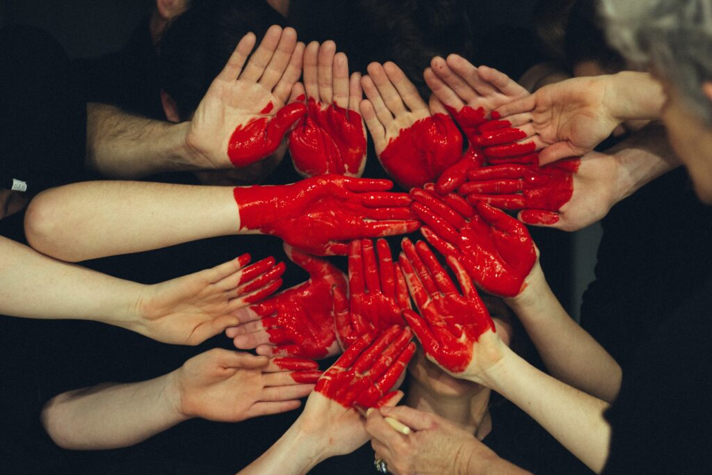 Volunteers' hands put together, making the shape of a heart.