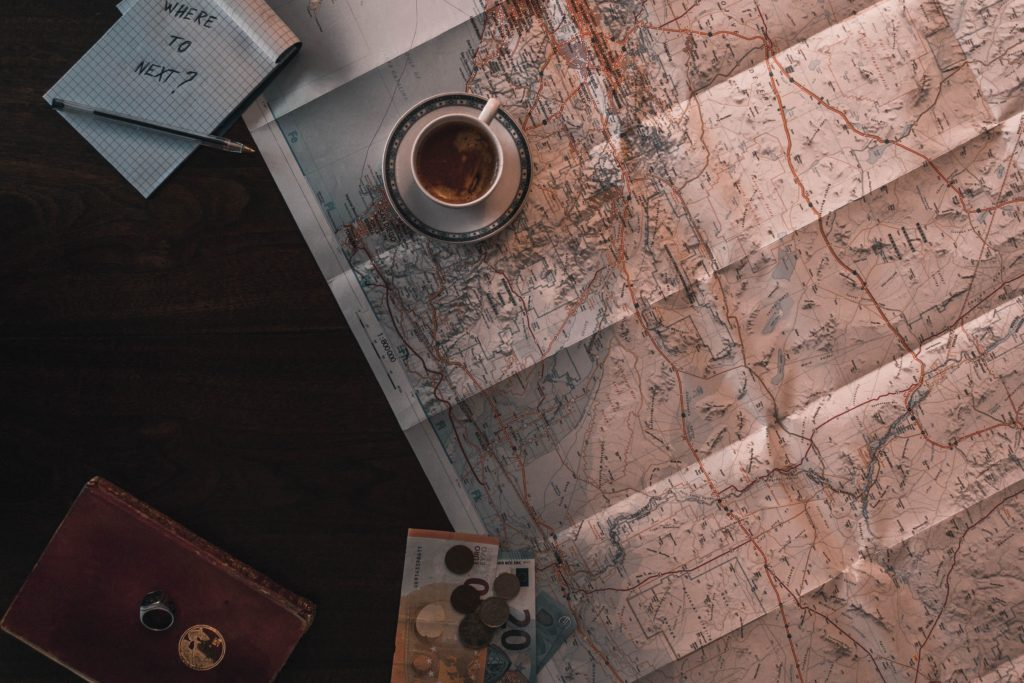 coffee cup, map, and money on table, planning a trip