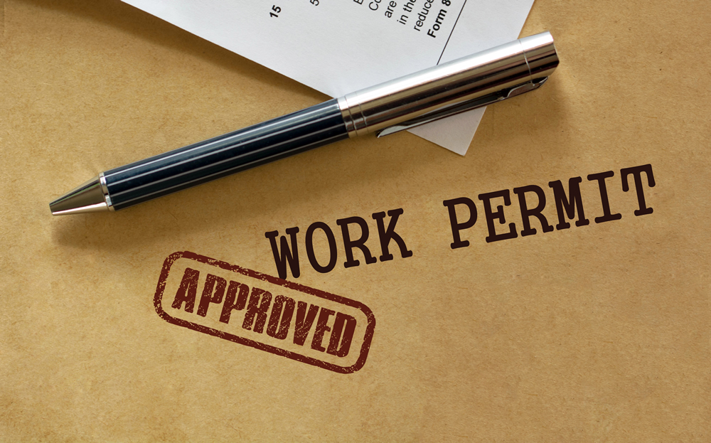 A pen and a piece of paper on a brown background; Text reads Work Permit Approved