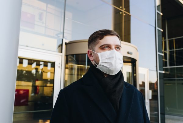 Man wearing face mask in front of a business building
