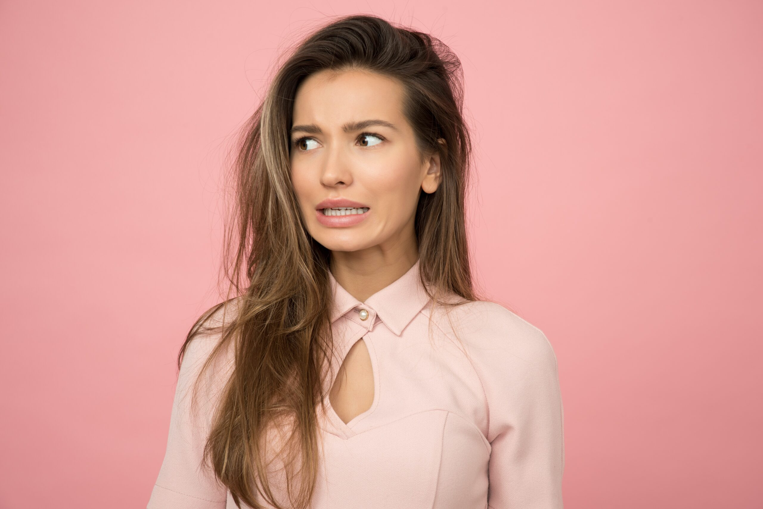 Woman wearing a pink top with an anxious facial expression