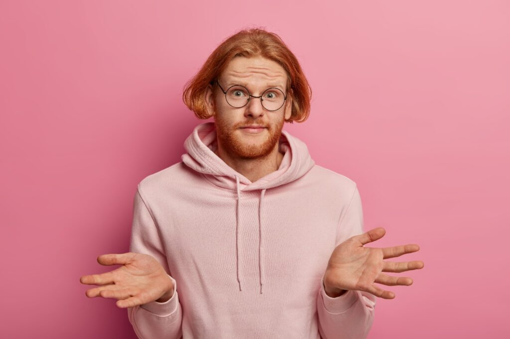 How to write a good cover letter? A ginger man in a pink sweatshirt looking confused.