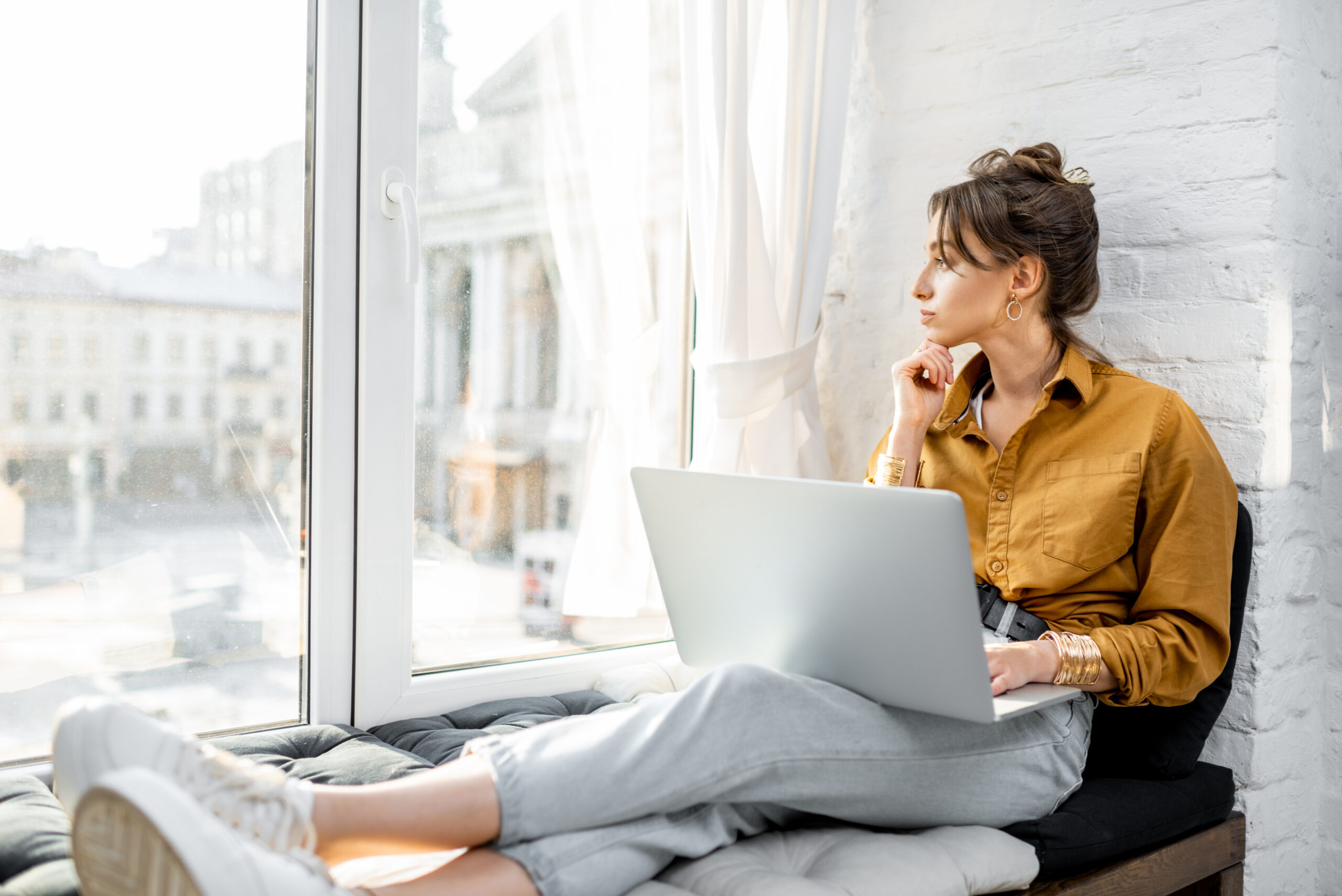 Woman working from home with laptop on the window sill